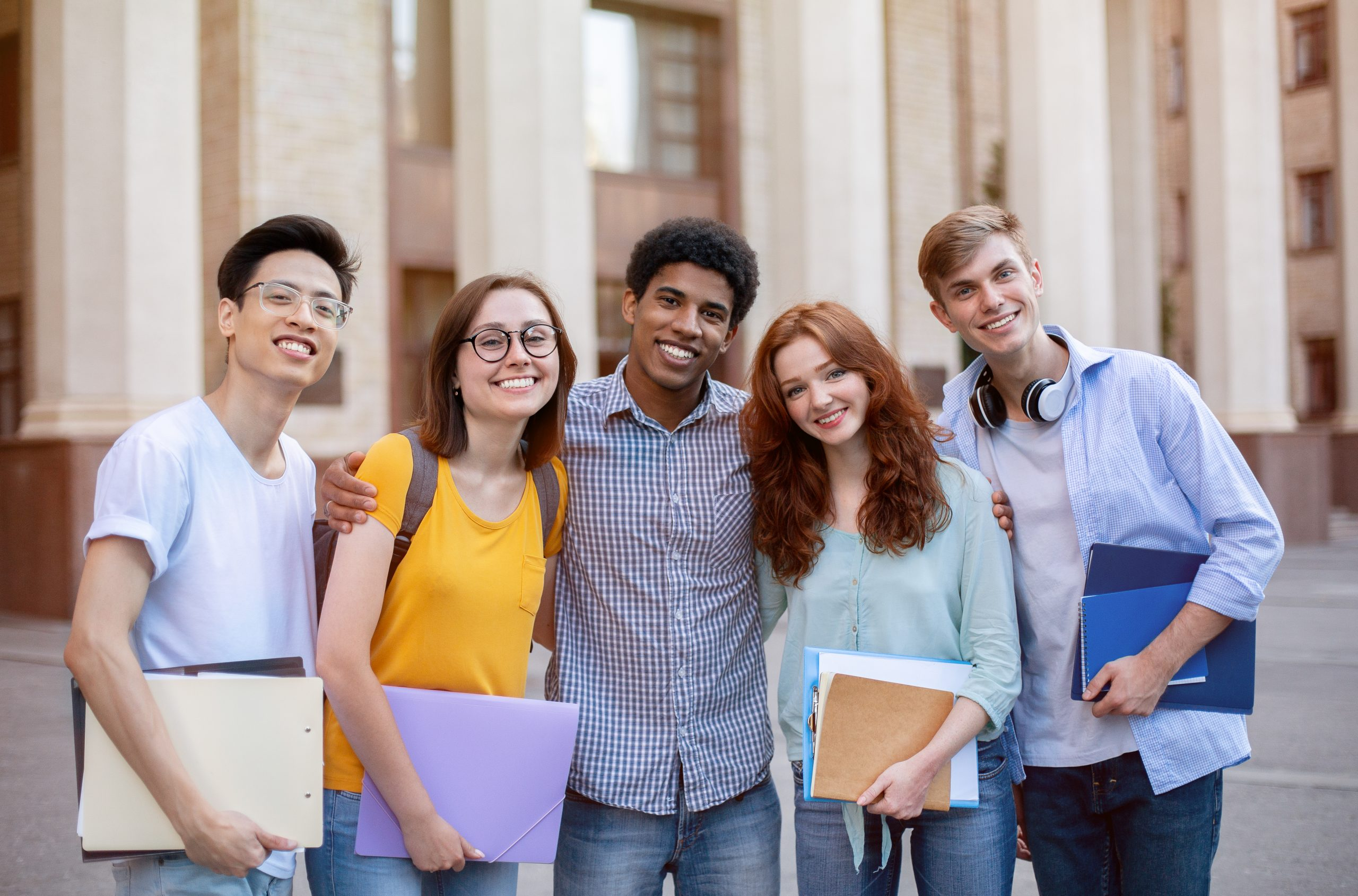 Happy Diverse Students Standing Together Near University Building Outdoors